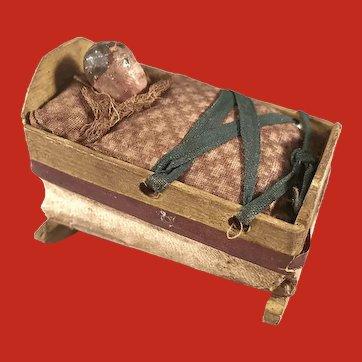 A baby in a cradle squeak toy, German circa 1850