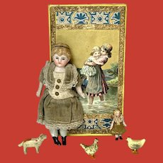 A bisque dollhouse doll with a tiny doll in cardboard box