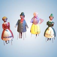 Four small wooden bristle dolls