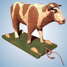 A sweet handpainted carved wooden cow pull toy