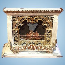 A tinplate dollhouse fireplace