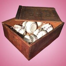 A dolls tea set in original wooden box