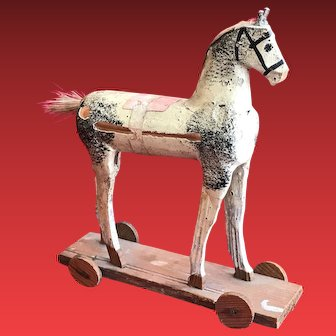 A small painted wooden horse on wheeled platform