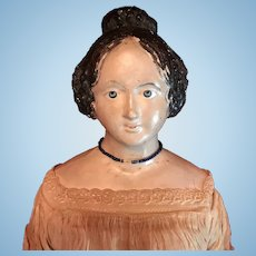 A large papier mache doll with unusual hairstyle, circa 1830