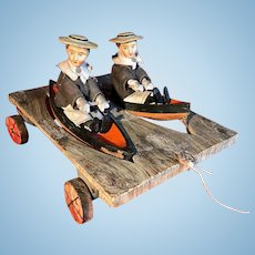 A charming  pull toy with two sailor boys in a rowing boat on a wheeled platform, German, late 19th Century