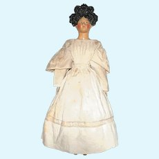 A lovely papier-maché lady doll with apollo knot coiffure