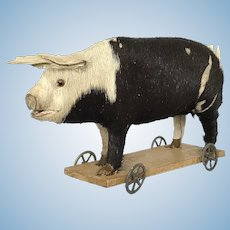 A cute toy pig on a wheeled platform