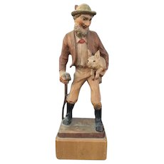 Wood Carving of an Pig Farmer Carrying a Piglet - Charming!