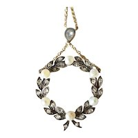 An antique  French laurel leaf circular pendant, pearl and diamond adorned, 1900c.