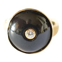 An eighteen carat gold ring/onyx front and centred diamond, 1925 to 1950.