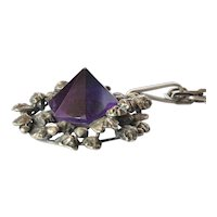 Pyrimid cut amethyst set in a pendant with based silver ( 835 ) surround; the pendant is on a silver (835 ) chain,1985c.