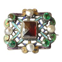 A square pieced enamel and gem set silver (800 ) brooch, late 19th. century.