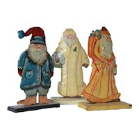 A trio of vintage enamelled tin, signed, Santa Clauses.