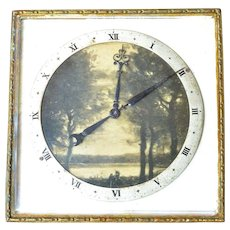 A vintage brass fold up 8 day travel clock with landscape scene in the dial center, Swiss made ,1940s.