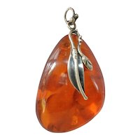 An early  vintage amber pendant with silver mount.