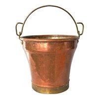 An antique copper/brass bucket.