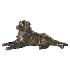 A vintage bronze plated metal retriever reclining dog.