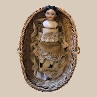 Small porcelain dollhouse doll in basket.