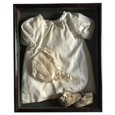 19th Century baby clothes in frame