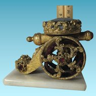 A continental brass novelty pin cushion modeled as a CANNON on a polished alabaster; c1800