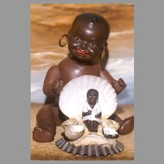 """MATRIX SUMMER SOUVENIR  - 3"""" tall Shell Art with Seated Black Bisque Figurine in Molded Clothes."""