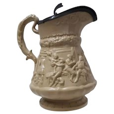 A Large Drabware Relief Molded Jug with Metal Lid