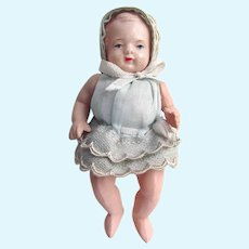 """3-1/4"""" Jointed Very Pale Celluloid Baby with Swivel Neck; Dressed in Pale Blue Synthetic with Beige Trimmed Lace"""