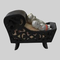 Cast Iron Filigreed Black Rocking Cradle with Silk Embroidered Cushion and Two Japan Dollies