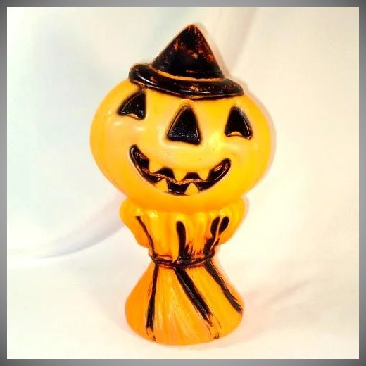this hollow hard plastic blow mold halloween table top or window decoration is a grinning jack olantern pumpkin heat atop a haystack or bundle of straw