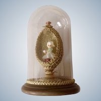 Napco Flower Girl Spaghetti Figurine in Hand Decorated Gold Easter Egg in Glass Dome with Wood Base