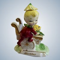 Mid-Century Norcrest Yellow Chrysanthemum November Month Pixie Elf Boy on Mum Flower Cart Ceramic Figurine F447