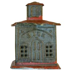 Old Tin Penny Bank In The Form Of A Bank Building With Red Painted Roof