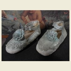 Antique soft fabric shoes with rosettes and embroidery.