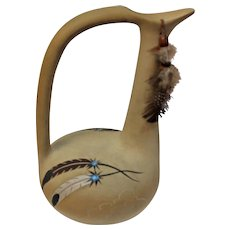 Betty Selby, of the Pueblo Pottery Company, a water jug with hand painted feathers and medallions and beads