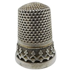 A French silver thimble with applied decoration. c 1860