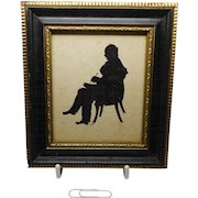 A small framed silhouette of a seated gentleman writing. c 1840