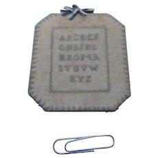 A miniature sampler pin cushion. c 1840