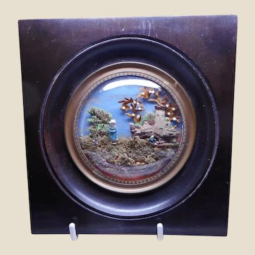 A framed diorama of miniature figures in a landscape. 19th century French.