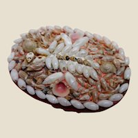 An oval pin cushion covered with tiny seashells. A Victorian souvenir.