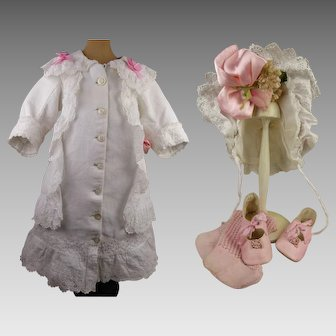 Four-piece Antique original French  white  pique doll  coat-dress with antique shoes, stockings and bonnet from ca 1890.