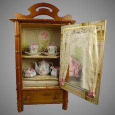 Antique faux-bamboo cabinet from the late 19th century with sweet tea set