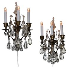 A pair of three light brass and crystal wall sconces