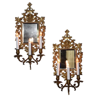 A pair of bronze mirrored appliques