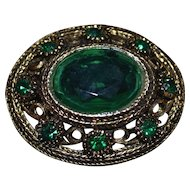 Vintage bronze brooch with green crystals
