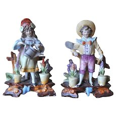 A charming pair of German bisque figures of children gardeners,