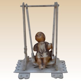 Sweet little bone dolls' house swing with wax child, late 19th century