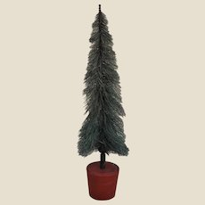 A vintage bristle bottle cleaner Christmas tree in wooden tub,