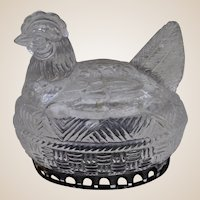 An antique glass candy container in the form of a chicken on nest,