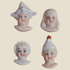 Four German bisque faces, circa 1900