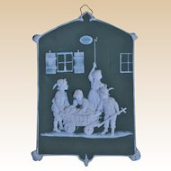 A German green bisque plaque of children taking a dog to the doctors, circa 1900